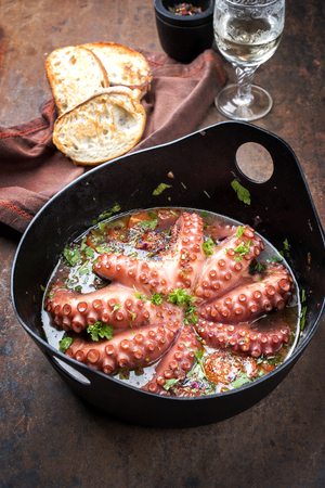 Traditional Greek octopus braised cooked with tomatoes and herbs in ouzo sauce as closeup in a cast-iron saucepan