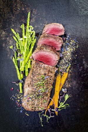 Traditional barbecue aged venison backstrap roast with green asparagus, carrots and herbs as top view on a rustic metal sheet  Stockfoto