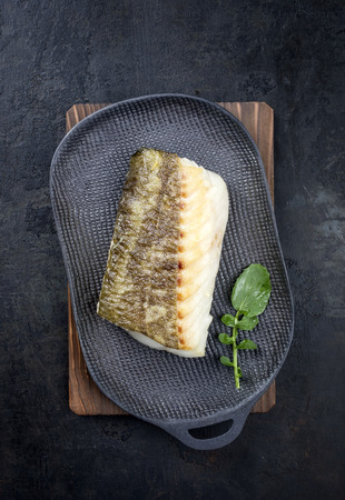 Fried Japanese skrei cod fish filet with wasabi lettuce as top view on a modern design plate