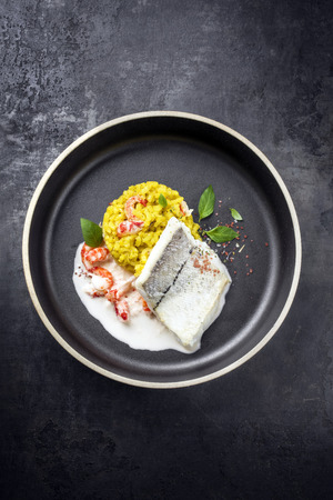 Fried haddock filet with saffron rice and shell prawns in crab sauce as top view on a modern design bowl with copy space Stock Photo