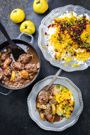 Traditional Iranian khoresh beh stew with chunks of lamb, quinces and saffron rice as top view in a cast-iron roasting dish and pewter plate 写真素材