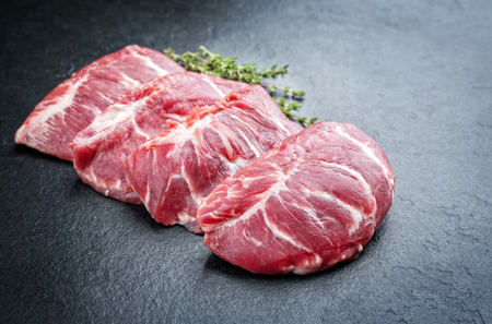 Traditional German raw pork cheeks with hers as closeup on a black board Stock Photo
