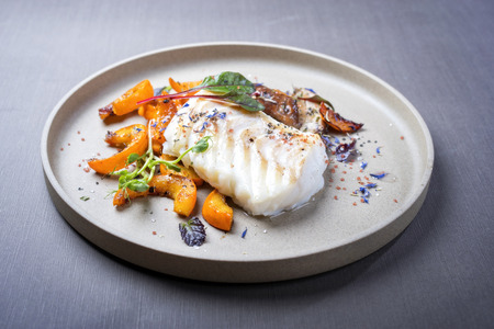 Fried Danish skrei cod fish filet with pumpkin, mushroom and lettuce as closeup on a modern design plate