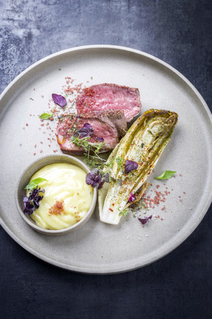 Barbecue wagyu point steak from beef sliced with chicory and mashed potatoes as top view on a modern design plate