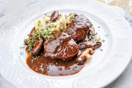 Traditional German braised pork cheeks in brown red wine sauce with mushroom and mashed potatoes as closeup on a classic design white plate