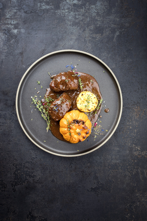 Traditional German braised pork cheeks in brown red wine sauce with fried mushed potatoes and pumpkin as top view on a modern design plate with copy space Stok Fotoğraf
