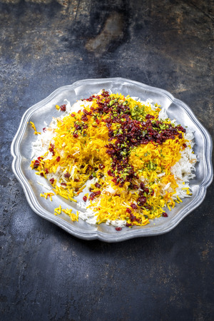 Traditional Iranian steamed saffron rice with berberis and pistachios as closeup on a pewter plate with copy space