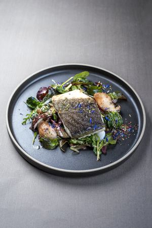 Fried Norwegian skrei cod fish filet with porcini mushroom and lettuce as closeup on a modern design plate