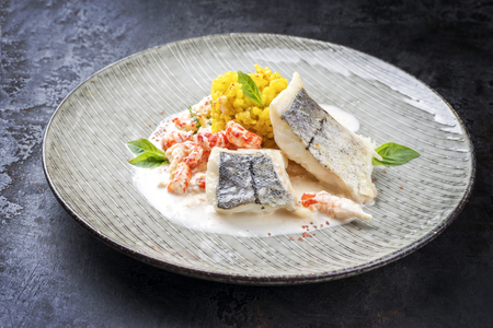 Fried haddock filet with saffron rice and shell prawns in crab sauce as closeup on a modern design plate Фото со стока