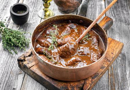 Carrilleras de cerdo estofado tradicional alemán en salsa de vino tinto marrón con champiñones y cebollas como primer plano en una cazuela