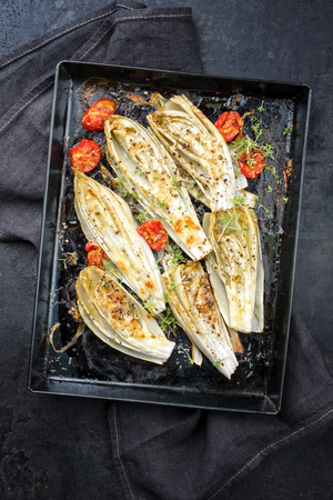 Traditional barbecue sliced chicory with tomatoes and herbs as top view on a rustic metal sheet 免版税图像