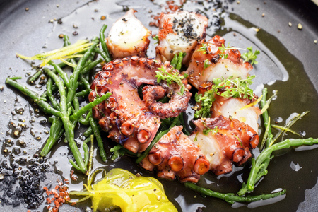 Traditional French octopus braised cooked with Salicornia, lemon curd and spice as top view on a modern design plate