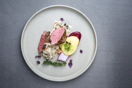 Barbecue wagyu point steak from beef sliced with chanterelle and mashed potatoes as top view on a modern design plate with copy space