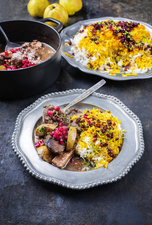 Traditional Iranian khoresh beh stew with chunks of lamb, quinces and saffron rice as closeup in a cast-iron roasting dish and pewter plate