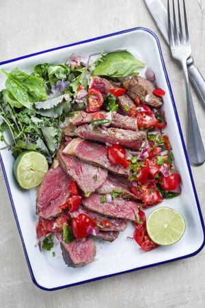 Traditional South American barbecue wagyu roast beef sliced with pico de gallo and salsa verde garnished with lettuce as top view in a rustic skilled Stok Fotoğraf