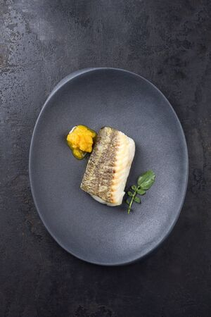 Fried Danish skrei cod fish filet with wasabi lettuce and lemon curd as top view on a modern design plate with copy space