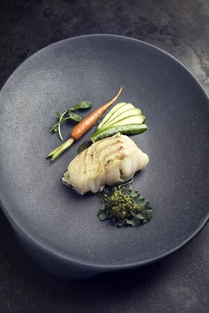 Fried Danish skrei cod fish filet with vegetable, lettuce and coriander pesto as top view on a modern design plate