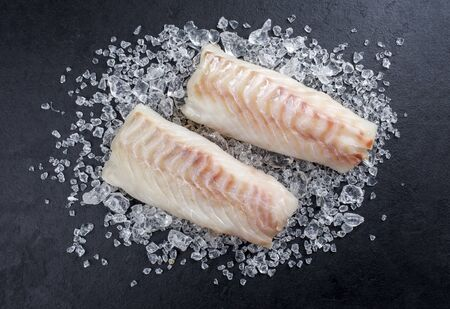 Raw Norwegian skrei cod fish filet as top view on crashed ice on a black board with copy space 免版税图像