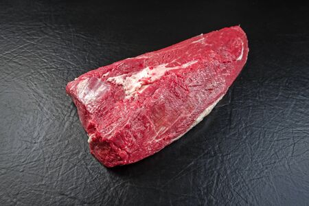 Raw wagyu mock tender roast beef as closeup on black background with copy space