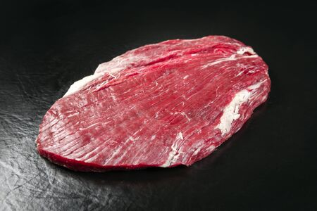 Raw dry aged wagyu flank steak as closeup on black background with copy space Stock Photo
