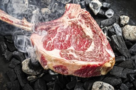 Traditional raw dry aged wagyu tomahawk steak on hot burning charcoal with smoke as closeup on a barbecue fire Stock Photo