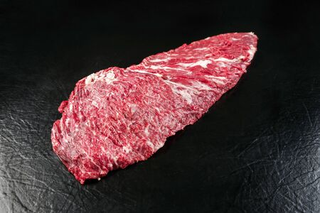 Raw wagyu skirt steak as closeup on black background with copy space