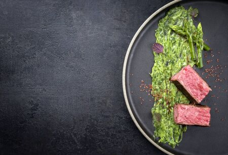Blanched green asparagus with barbecue dry-aged wagyu fillet steak and avocado coriander relish as closeup on a modern design plate with copy space Banco de Imagens
