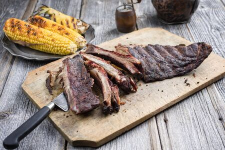 Barbecue spare ribs St Louis cut with hot rub and corn  on a wooden cutting board Imagens
