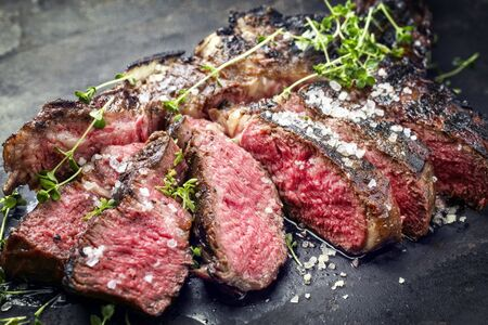 Traditional barbecue dry-aged wagyu tomahawk steak sliced with salt and herb as closeup on a rustic old black board Stock Photo