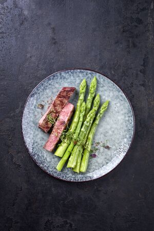 Barbecue dry aged wagyu roast beef steak with blanched green asparagus and herbs as top view on a modern design plate with copy space