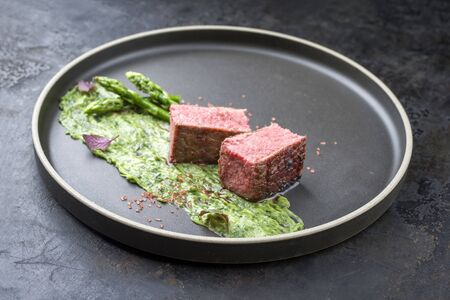 Blanched green asparagus with barbecue dry-aged wagyu fillet steak and avocado coriander relish as closeup on a modern design plate