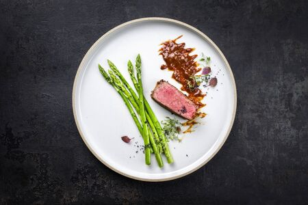 Blanched green asparagus with barbecue dry aged wagyu fillet steak and hot sauce as top view on a modern design plate with copy space