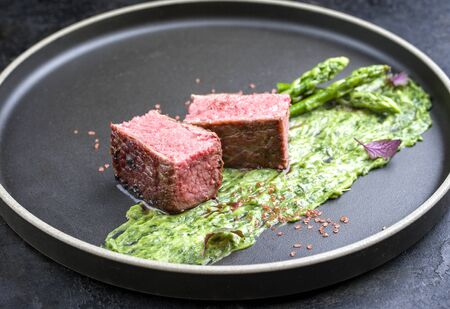 Blanched green asparagus tips with barbecue dry aged wagyu fillet steak and avocado coriander relish as closeup on a modern design plate Banco de Imagens
