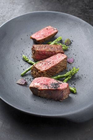 Barbecue dry aged wagyu fillet steak with blanched green asparagus tips and herbs as closeup on a modern design plate