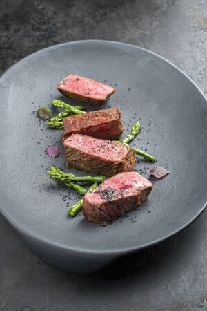 Barbecue dry-aged wagyu fillet steak with blanched green asparagus tips and herbs as closeup on a modern design plate
