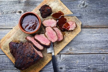 Barbecue dry aged wagyu tri tip steak with BBQ sauce as dip as top view on a wooden cutting board with copy space Stok Fotoğraf