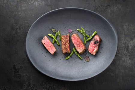 Barbecue dry aged wagyu fillet steak with blanched green asparagus tips and herbs as top view on a modern design plate with copy space Banco de Imagens