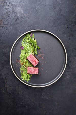 Blanched green asparagus tips with barbecue dry aged wagyu fillet steak and avocado coriander relish as top view on a modern design plate with copy space Banco de Imagens