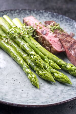 Barbecue dry aged wagyu roast beef steak with blanched green asparagus and herbs as closeup on a modern design plate with copy space