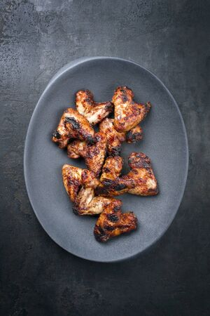 Traditional barbecue chicken wings with hot chili sauce as top view gray modern design bowl with copy space