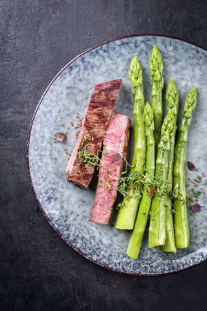 Barbecue dry aged wagyu roast beef steak with blanched green asparagus and herbs as top view on a modern design plate