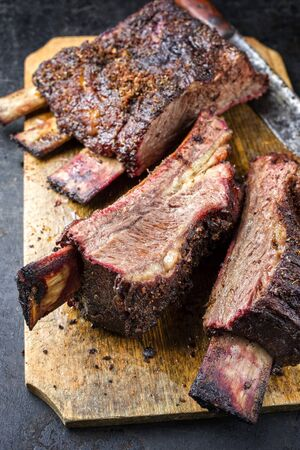 Barbecue sliced chuck beef ribs with hot rub as closeup  on a wooden cutting board  写真素材