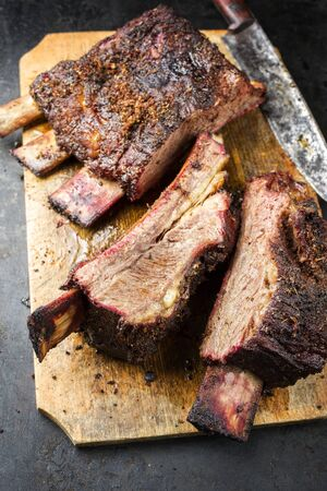 Barbecue sliced chuck beef ribs with hot rub as closeup on a wooden cutting board