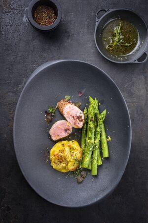 Fried Iberian pork fillet sliced with blanched green asparagus and potato gratin dauphinois with spice as top view on a cast iron design plate  Banco de Imagens