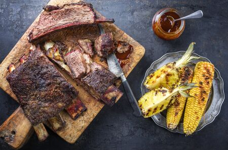 Barbecue sliced chuck beef ribs with hot rub with pineapple and corn as top view sliced on a wooden cutting board  스톡 콘텐츠