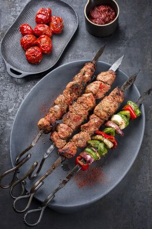 Traditional Russian shashlik on a barbecue skewer with vegetable and sumach paste as top view on a modern design plate Фото со стока - 129768449