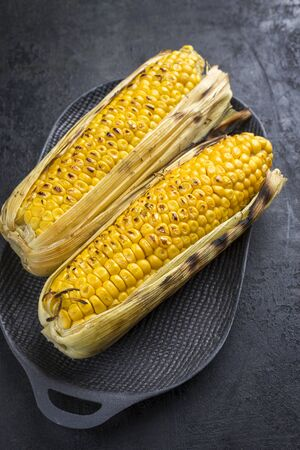 Traditional barbecue corn green as closeup on a cast iron design plate