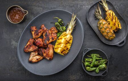 Exotically barbecue chicken wings with hot chili sauce, jalapeno and pineapple as top view on a cast iron plate Stock Photo - 129768638