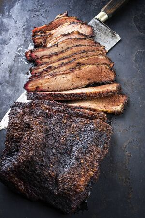 Traditional smoked barbecue wagyu beef brisket offered as closeup with knife on an old rustic board with copy space