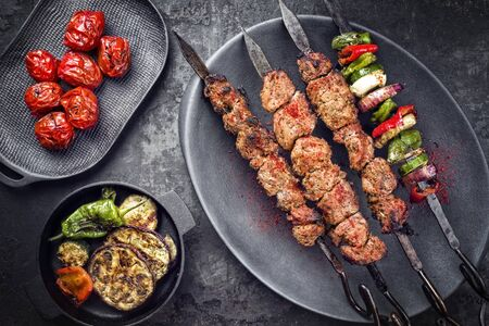 Traditional Russian shashlik on a barbecue skewer with vegetable and sumach paste as top view on a modern design plate Фото со стока - 129768644